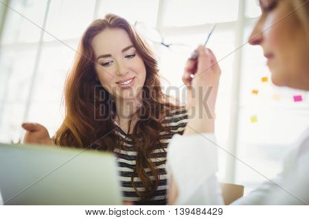 Young businesswoman discussing with female colleague while using laptop in creative office