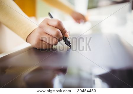 Cropped image of businesswoman writing on paper in creative office