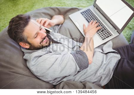 High angle view of happy businessman using laptop and mobile phone while relaxing on bean bag at creative office