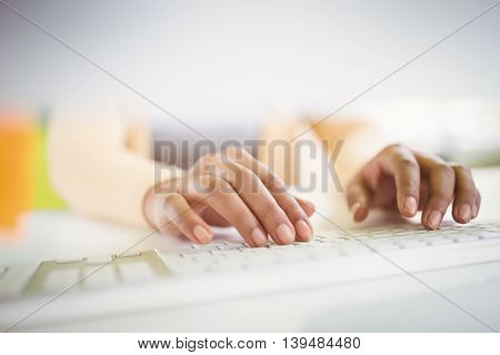 Close-up of of businesswoman typing on keyboard in creative office