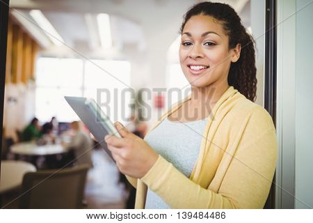 Portrait of happy businesswoman using digital tablet in office cafeteria