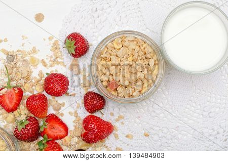Ripe and tasty strawberries with scattered muesli on white background