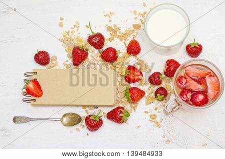 Blank notebook with craft brown pages ripe strawberries and oat muesli for breakfast