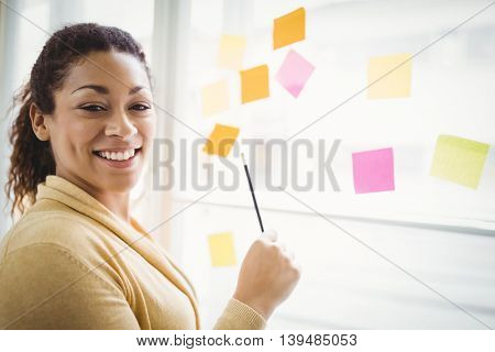 Portrait of young businesswoman writing on adhesive notes in creative office