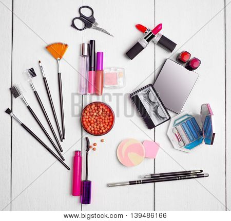 Accessories for make-up on wooden background .