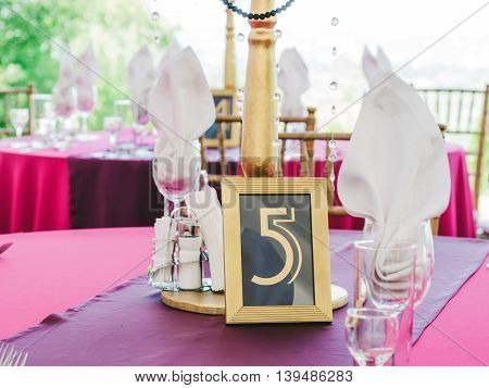 Wedding table with sign number five. Guests wedding table with sign of number 5