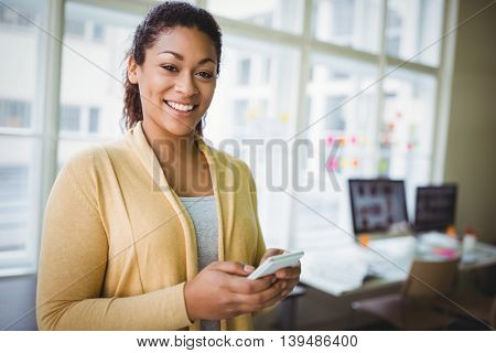 Porrait of young businesswoman smiling while using phone at creative office