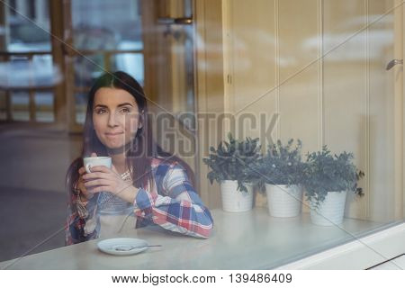 Thoughtful beautiful young woman having coffee at cafe