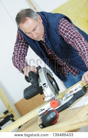 portrait of carpenter cutting wood using table saw