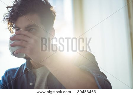 Young man drinking coffee at cafe