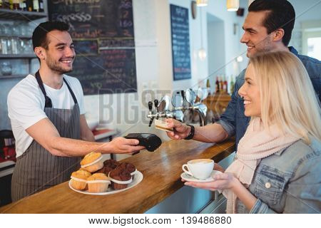 Happy customers paying through card while looking at male barista in cafe