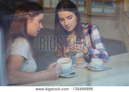 Beautiful woman showing cellphone to young friend at cafe