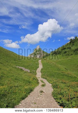 Summer scene in Glarus Canton Swiss Alps. Hiking trail leading towards Mt Dejebstogg. Cloud.