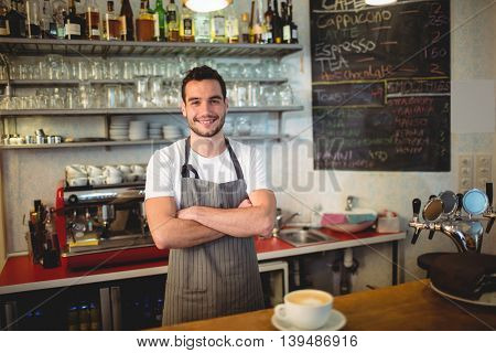 Portrait of confident male barista standing with arms crossed at coffee house