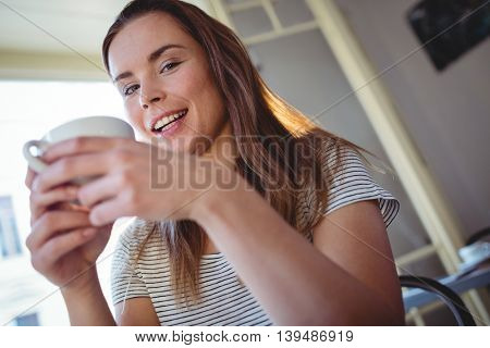 Portrait of happy attractive woman with coffee at cafe