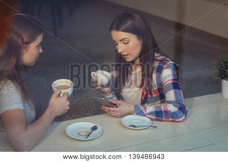 Beautiful young woman using cellphone with female friend at cafe