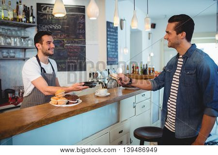 Happy young customer giving credit card to male barista at coffee shop
