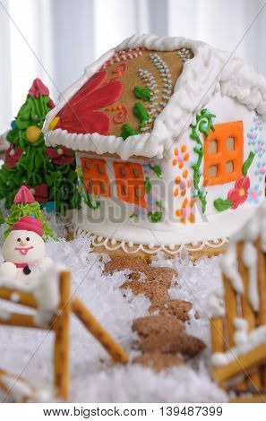Gingerbread house painted in ethnic style among the trees and snow