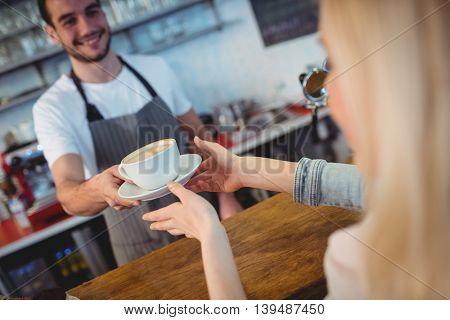 Tilt shot of young male barista serving coffee to woman at cafe