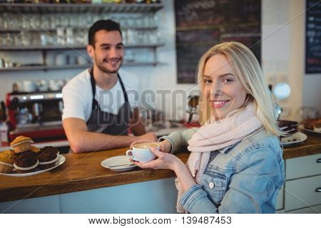 Portrait of beautiful young woman holding coffee with waiter at cafe