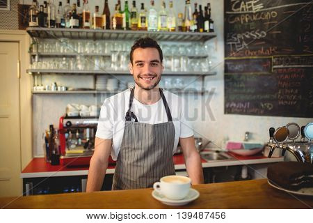 Portrait of confident young waiter with coffee at counter in cafe