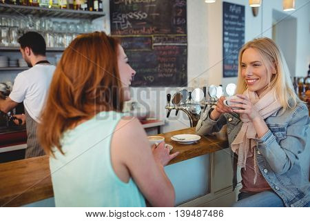 Happy beautiful young woman talking to female friend at cafe counter