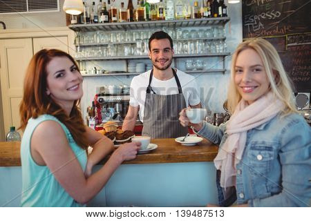 Portrait of young waiter with happy female customers at coffee shop