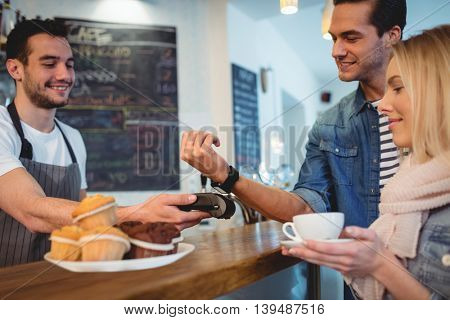 Happy young customers with waiter at coffee shop