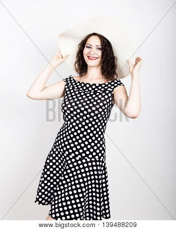 beautiful young brunette woman holding a broad-brimmed hat, she expression of different emotions. wears a dress with polka dots.