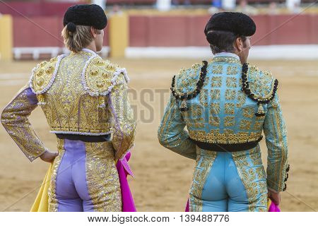 Andujar SPAIN - september 10 2010: Spanish Bullfighters looking bullfighting the Bullfighter on the left dressed in suit of lights of colors red and gold and the right color pistachio and gold in Andujar Spain