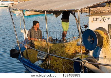PELOPONNESE, GREECE - JULY 16, 2016: A fisherman prepares his nets in his boat on July 10, 2016 in Petalidi of Peloponnese, Greece. Fishing in wooden traditional boats remains an important part of the local economy in Greece.