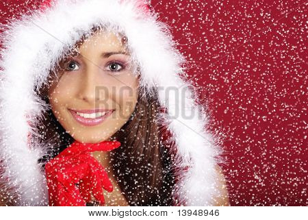 Portrait of beautiful woman wearing sexy santa claus clothes on red and snow background