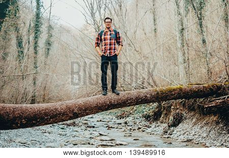 Hiker young man standing on fallen tree trunk over the mountain river in forest