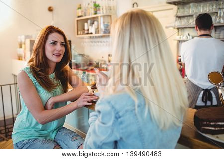 Beautiful young woman talking to female friend at cafe counter