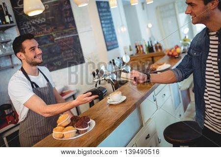 Happy customer and waiter with card and reader at coffee shop