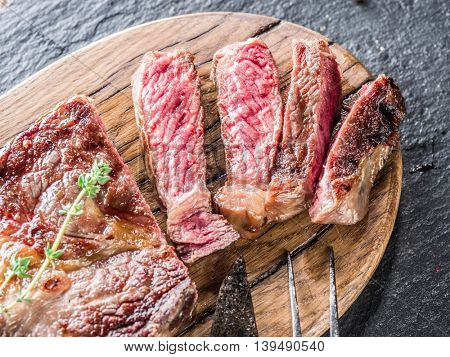 Medium Ribeye steak with spices on the wooden tray.