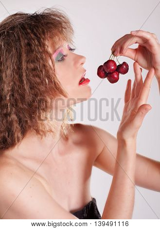 Beautiful young woman preparing to eat four red cherries