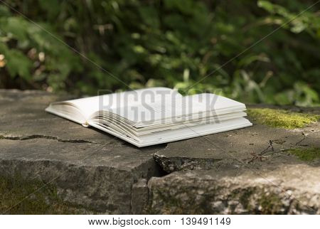 Open book on the stone bench in the park.