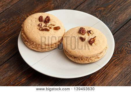Two Traditional French Beige Macarons On Plate, Wooden Background