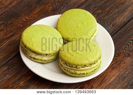 Three Traditional French Pistachio Macarons On Plate, Dark Wooden Background