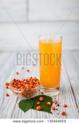 Sea- buckthorn juice , glasss, leaves  plate  wooden