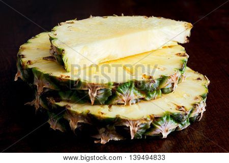Round Pineapple Slices With Skin Isolated On Dark Wood.