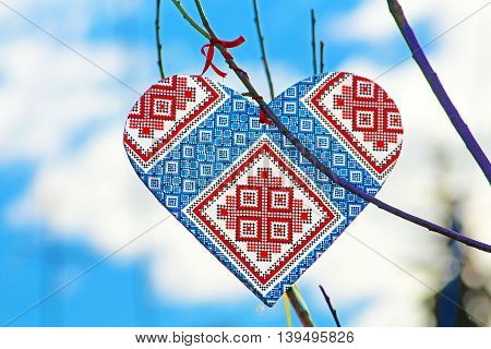 Hand made heart in the style of Ukrainian vyshyvanka on the handmade tree which children made due to Europe Day in Vinnytsia, Ukraine. Vyshyvanka is the colloquial name for the embroidered shirt in Ukrainian national costume