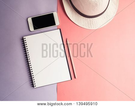 Top view of open spiral notebook brown pencil mobile phone and white hat on two tone pastel violet and orange background