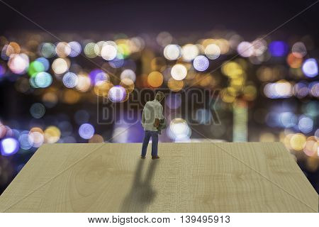 mini man stand on wood plate and city life bokeh night wait for him - can use to display or montage on product or concept of dicision
