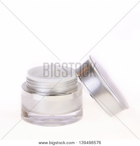 glass jar of beauty face cream with cap, on white background.