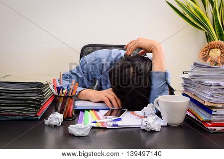 Businessman asleep at office desk with finance sheet calculator and coffee. concept for overworked