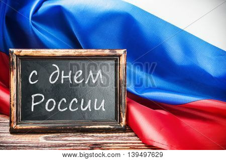 Russian flag on a wooden table and a blackboard with the text. writing on the blackboard in Russian