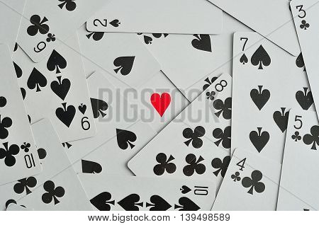 A heart in the middle of black suits of playing cards