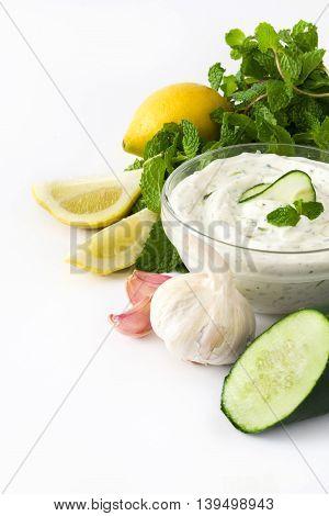 Tzatziki sauce, lemon,cucumber, garlic, parsley and mint isolated on white background
